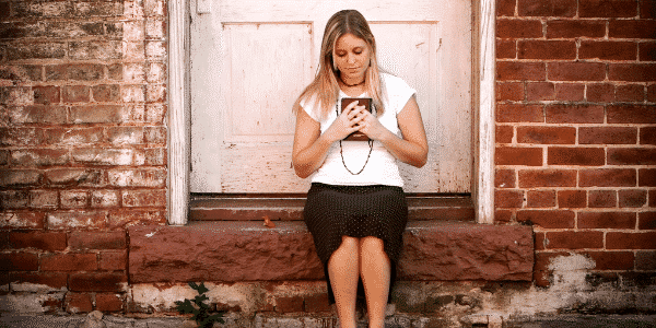 woman sitting on steps holding tablet